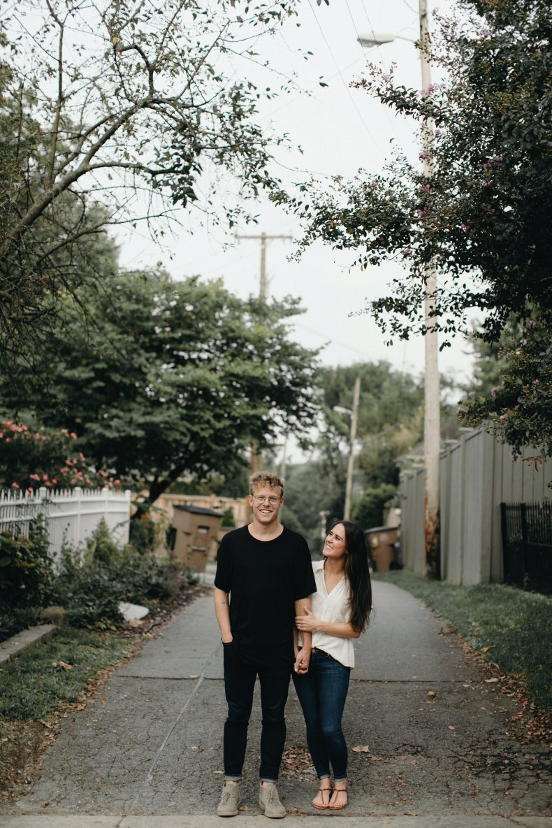 hip couple standing in alleyway