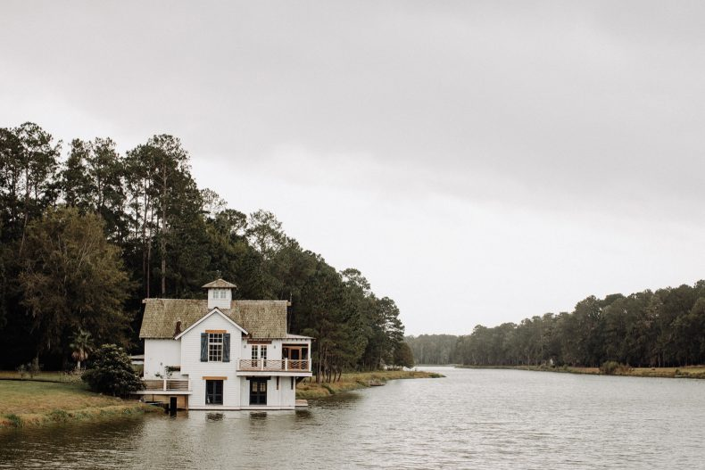 little white house with dark blue shutters built on edge of river in savannah