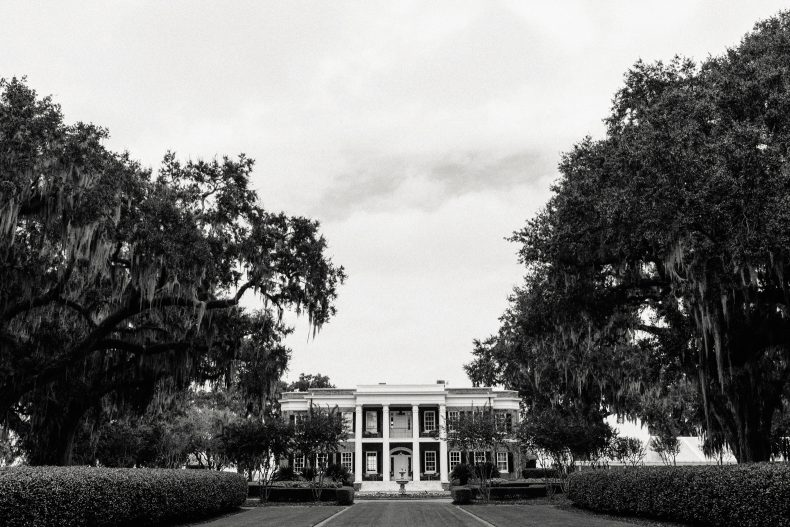 black and white image of historic ford plantation nestled between spanish moss trees on cloudy day
