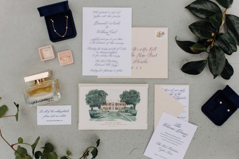 arrangement of things laying on ground including wedding invitation with watercolor of ford plantation on front