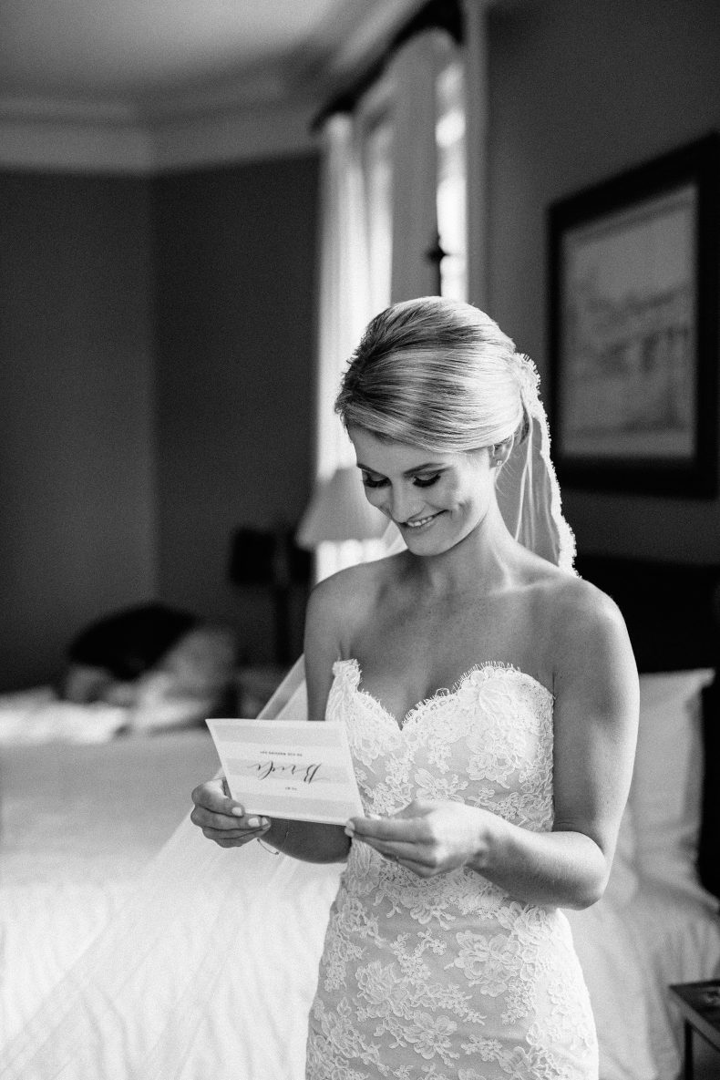 bride in lace sweetheart dress smiling while reading letting from the groom near window