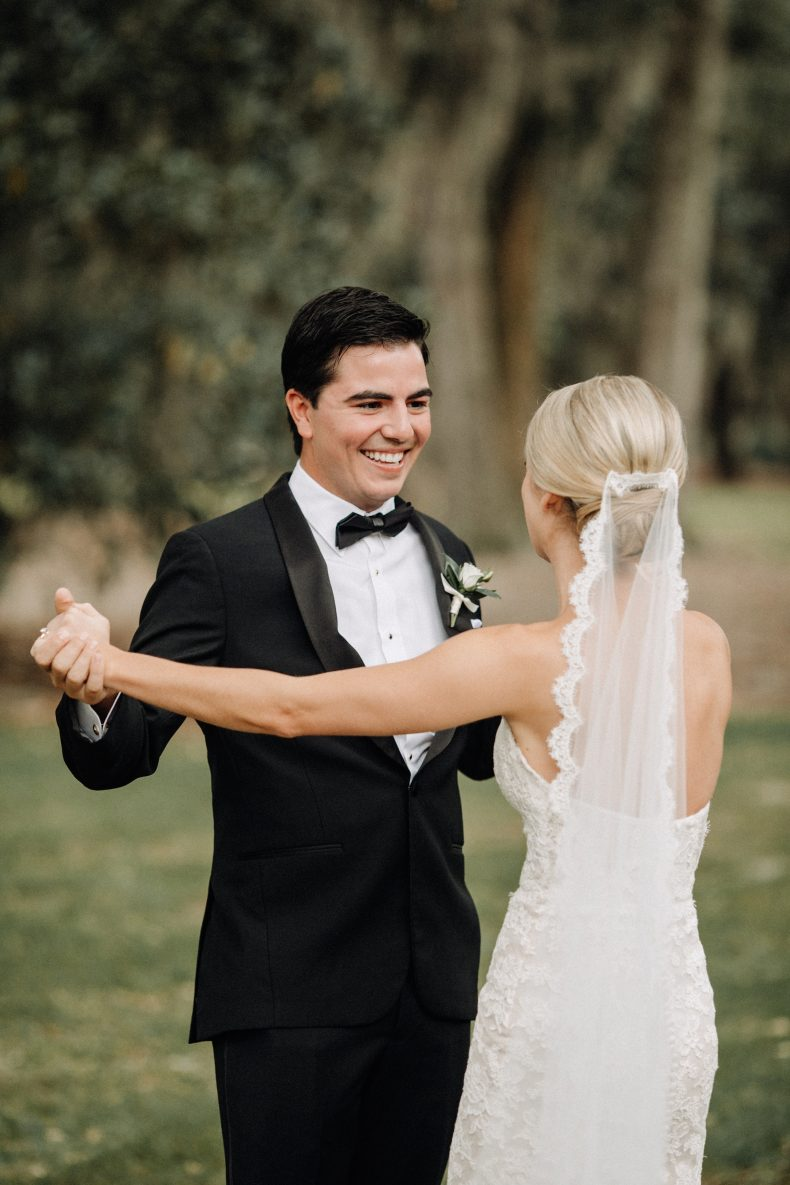 groom smiling while seeing his bride in lace wedding dress for the first time